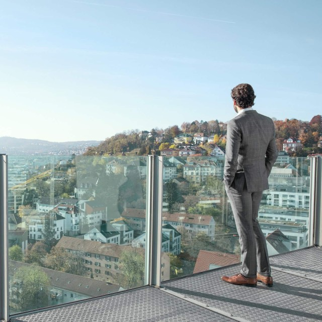 Man looks at a city from a glass balcony