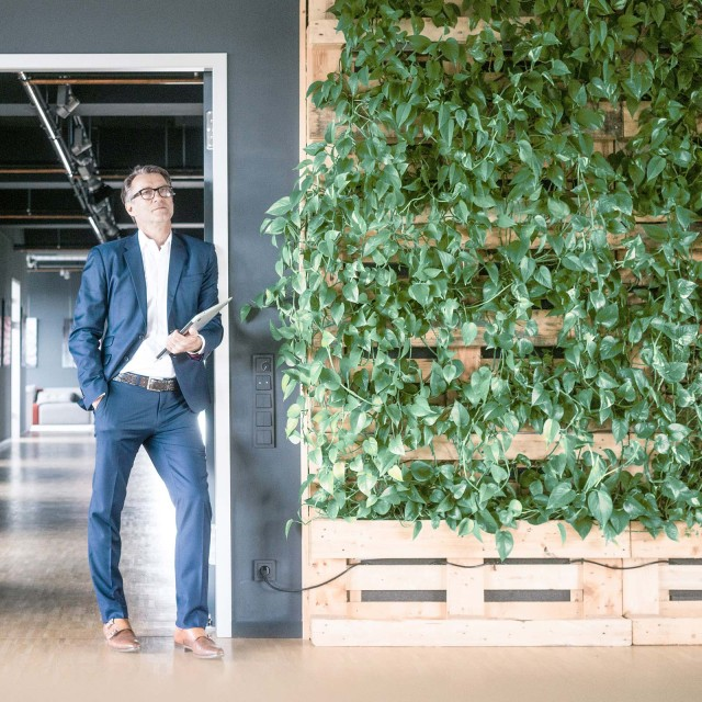 Man in front of office next to green wall